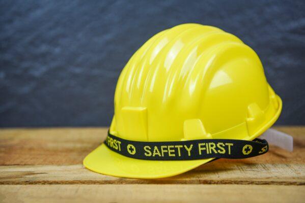 safety-first-concept-yellow-hard-safety-wear-helmet-hat-engineer-worker-helmet-on-wooden-background