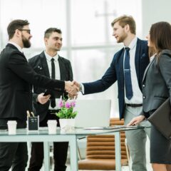 handshake of business partners after signing the contract in the workplace in a modern office