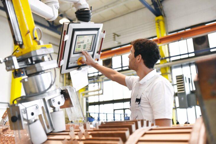 Industrie 4.0 der Mensch bedient die Maschine, die die Arbeit für ihn macht